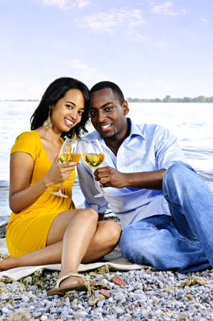 man drinking water: Young romantic couple celebrating with wine at the beach