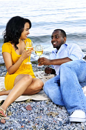 Young romantic couple celebrating with wine at the beach looking at each other photo