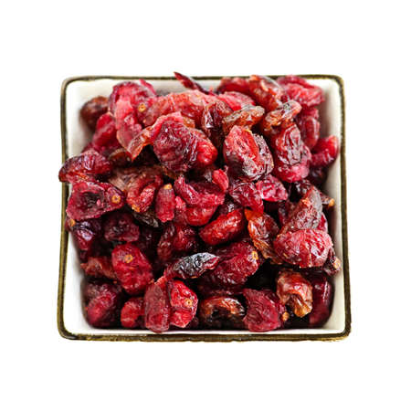 Bowl of dried cranberries isolated on white background photo
