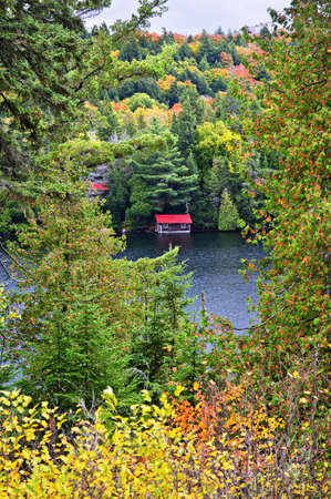 Boathouse on lake through fall forest with colorful trees