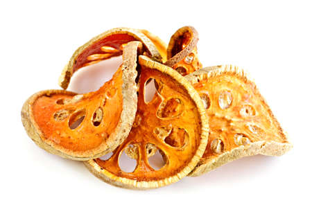Slices of dried bael fruit on white background photo