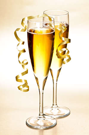 Two full champagne flutes with sparkling wine and ribbon