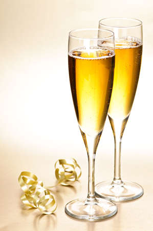 Two full champagne flutes with sparkling wine and ribbon photo