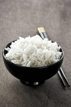 White steamed rice in asian bowl with wooden chopsticks