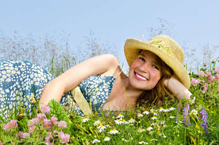 Young teenage girl laying on summer meadow amid wildflowers in straw hat photo