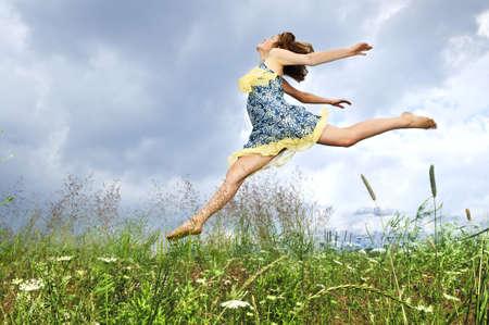 夏の草原の野生の花の中でジャンプ若い 10 代の少女