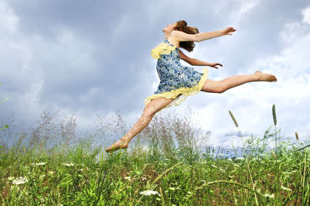 Young teenage girl jumping in summer meadow amid wildflowers Stok Fotoğraf - 5799023