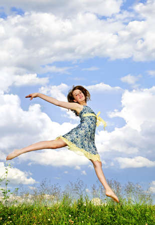 teenage girls: Young teenage girl jumping in summer meadow amid wildflowers