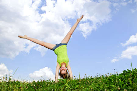 Young teenage girl doing cartwheel in a summer meadow photo