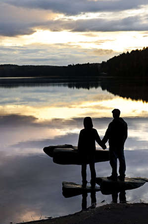 algonquin park: Sun setting over tranquil lake with people watching in silhouette