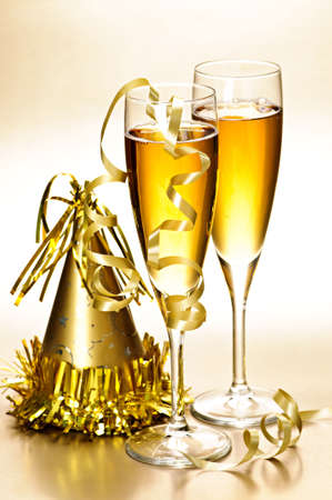 gold flute: Two full champagne flutes with party hat and ribbons