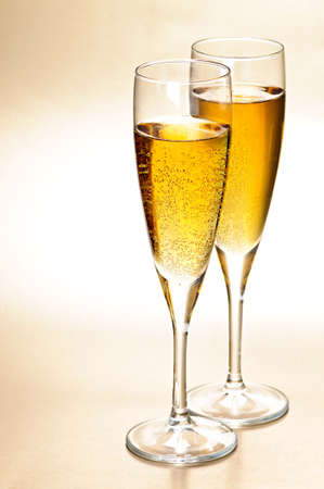 Two full champagne flutes with sparkling wine