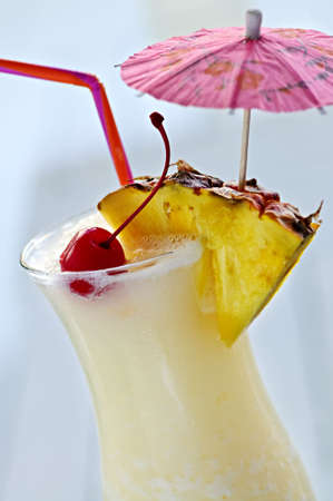 alcoholic drink: Pina colada drink in hurricane cocktail glass isolated on white background