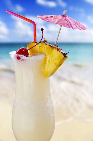 Pina colada beber en vaso de coctel con playa tropical en segundo plano Foto de archivo