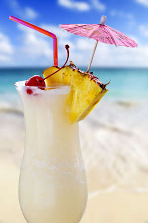 frozen fruit: Pina colada drink in cocktail glass with tropical beach in background