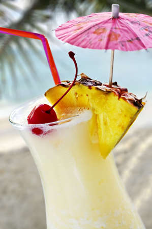 toothpick: Pina colada tropical drink at sandy beach on the ocean