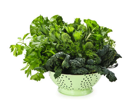 Dark green leafy fresh vegetables in metal colander isolated on white