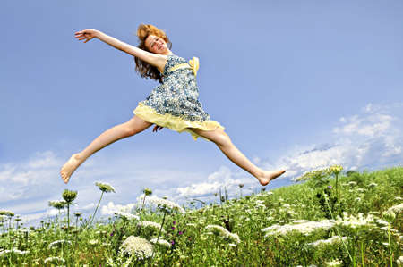 Young teenage girl jumping in summer meadow amid wildflowers photo