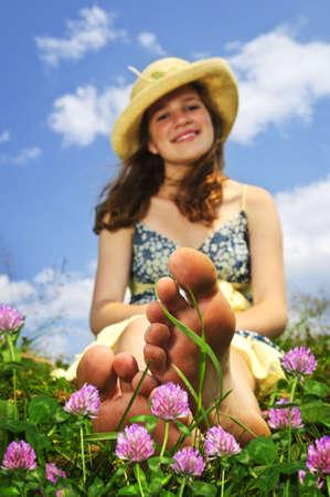 麦わら帽子の野生の花の中で夏の草原の上に座って若い 10 代の少女