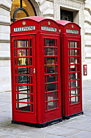 old english: Two red telephone boxes near on London sidewalk Stock Photo