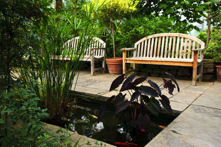 koi fish pond: Lush green garden with stone landscaping, koi pond and benches Stock Photo