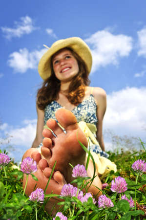 bare feet toes: Young teenage girl sitting on summer meadow amid wildflowers in straw hat Stock Photo