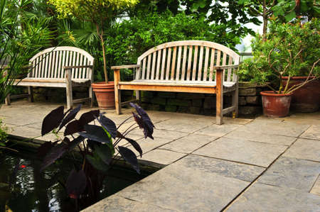 pave: Lush green garden with stone landscaping, pond and benches Stock Photo