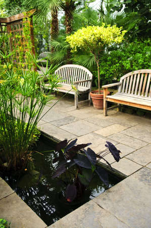 garden pond: Lush green garden with stone landscaping, pond and benches Stock Photo