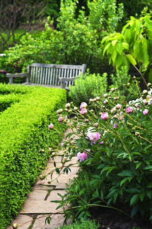 Lush green garden with stone landscaping, flowers, hedge and bench