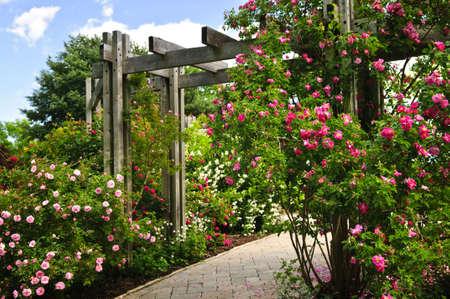 Weelderige groene tuin met steen land s cap ing, bloemen en prieel