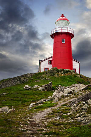 newfoundland: Red lighthouse on hill against stormy sky in Ferryland Newfoundland