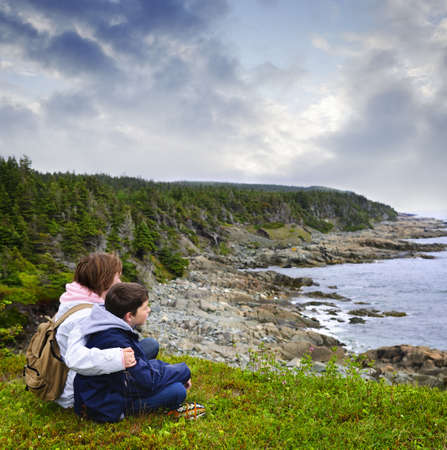 Children looking at coastal view of rocky Atlantic shore in Newfoundland, Canada photo