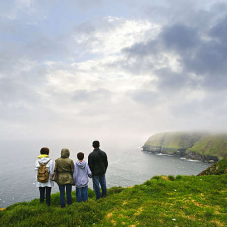 Family looking from cliff at Cape St. Mary's Ecological Bird Sanctuary in Newfoundland, Canada photo