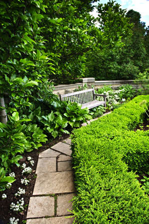 Lush green garden with stone landscaping, hedge, path and bench Imagens