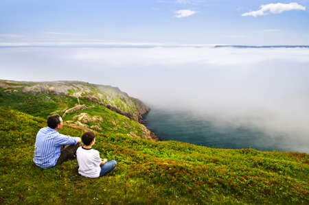foggy hill: Father and son looking at foggy ocean on Signal Hill, Newfoundland