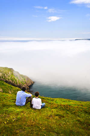 Father and son looking at foggy ocean on Signal Hill, Newfoundland