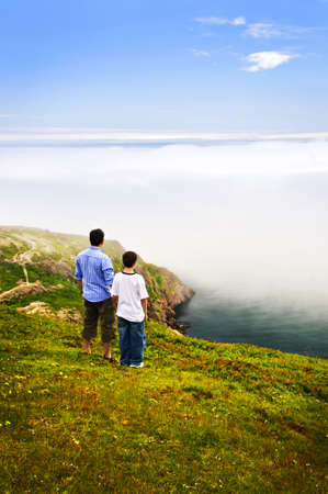 Father and son looking at foggy ocean on Signal Hill, Newfoundland photo