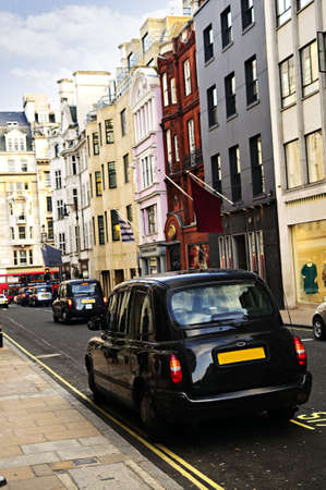 London street with taxicab and shops on sunny day