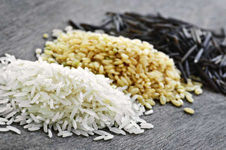 basmati: Three piles of white, brown and wild black uncooked rice Stock Photo
