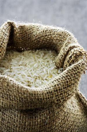 Raw long grain white rice grains in burlap bag photo