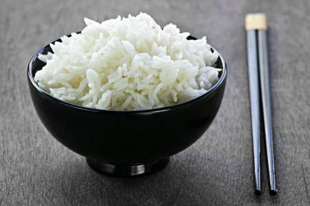 White steamed rice in black round bowl with chopsticks Banco de Imagens
