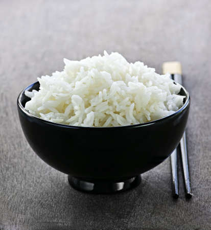 steamed: White steamed rice in black round bowl with chopsticks Stock Photo