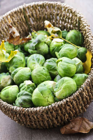 Basket of green brussels sprouts with autumn leaves
