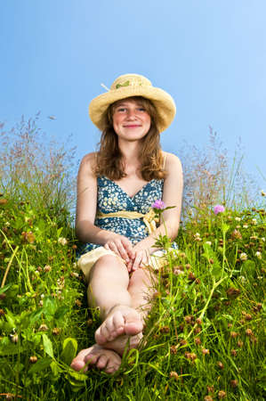 Young teenage girl sitting on summer meadow in straw hat photo