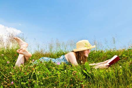 Jonge tiener meisje lees boek in de zomer weide met stro hoed