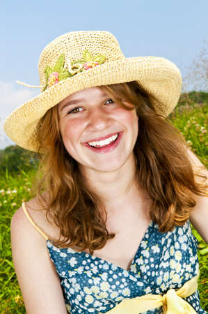 Portrait of young teenage girl smiling on summer meadow in straw hat Stock Photo - 6219936