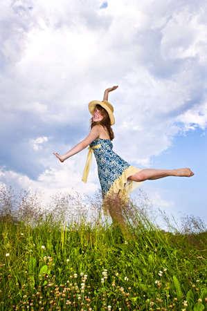 Young teenage girl dancing in summer meadow amid wildflowers
