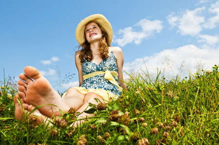 youngster  girl: Young teenage girl sitting on summer meadow barefoot