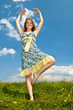Young teenage girl dancing in summer meadow amid wildflowers photo