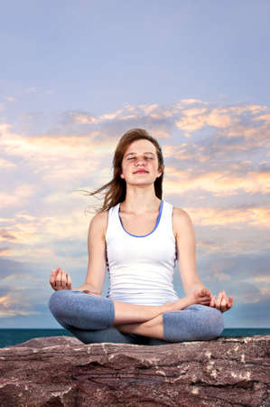 Portrait of young teenage girl practicing yoga at sunset photo